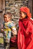 Mutter im Rot und Tochter in Nepal Lizenzfreie Stockfotos