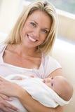 Mutter im Wohnzimmer mit Schätzchen Stockfoto