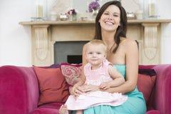 Mutter im Wohnzimmer mit Schätzchen lizenzfreie stockfotos