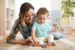 Mutter ist, Kind beibringend, wie man Xylophonspielzeug spielt lizenzfreie stockfotos