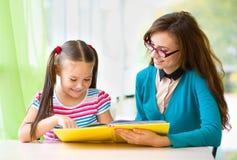 Mutter ist Lesebuch mit ihrer Tochter lizenzfreie stockfotografie
