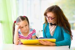 Mutter ist Lesebuch mit ihrer Tochter stockbild