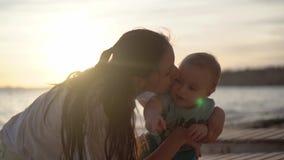 Mutter küsst ein Baby, das etwas mit Begeisterung nahe Meer in der Zeitlupe zeigt stock video footage