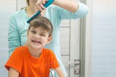 Mutter kämmt ihre siebenjährige Tochter im Badezimmer Stockbilder