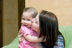 Mutter küßt Tochter lizenzfreies stockbild
