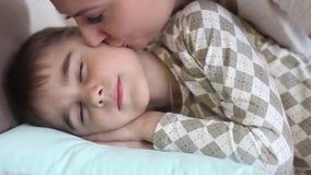 Mutter küsst den kleinen Sohn, während er schläft Der Sohn wacht auf, eine gute Laune habend stock video footage