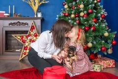 Mutter küsst die wenige Tochter am Weihnachtsfeiertag und zu Hause sitzt nahe einem Weihnachtsbaum lizenzfreies stockbild