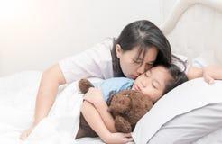 Mutter küsst ihre Tochter in der Backe beim Legen auf Bett lizenzfreie stockfotografie