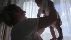 Mutter-Kinder-Verhältnis, glückliche Mama zieht in Hände Baby oben am Raumhintergrund des Fensters auf stock video