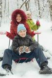 Mutter, kleiner Sohn und Tochter fahren auf Schlitten Stockfotos