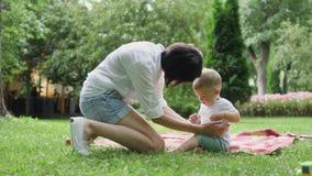 Mutter kommt zu einem jammernden kleinen Sohn auf einem Plaid im Park und erspart ihm stock footage