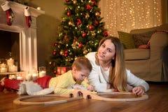 Mutter lächelt für das Foto nahe ihrem Sohnspielen lizenzfreies stockbild