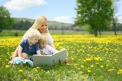 Mutter-Lesegeschichten-Buch zu zwei Kleinkindern draußen in Meado Lizenzfreie Stockfotos