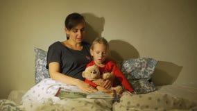 Mutter-Lesegutenachtgeschichten zu ihrem Kind stock footage