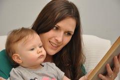 Mutter liest ein Buch zu einer Babytochter Stockfotos