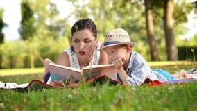 Mutter liest ein Buch zu ihrem Sohn im Park, der auf der Wolldecke liegt stock video footage