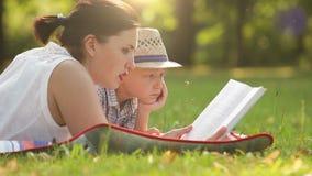 Mutter liest ein Buch zu seinem Sohn während auf dem Picknick im Park stock video