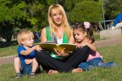 Mutter liest zu den Kindern des Buches auf einer Lichtung innen Lizenzfreie Stockfotografie