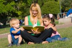 Mutter liest zu den Kindern des Buches auf einer Lichtung innen Lizenzfreies Stockbild