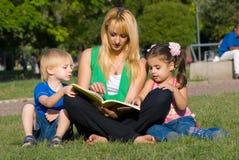 Mutter liest zu den Kindern des Buches auf einer Lichtung innen Stockfotos