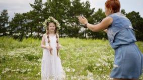 Mutter macht Foto ihrer Tochter im Kleid mit Kranz auf Kopf in der Blumenwiese