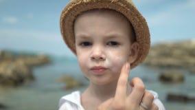 Mutter maskiert ihren Sohn mit sunblock Creme stock footage