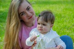 Mutter mit Baby in der hellen Kleidung auf einem rosa Plaid auf dem gr?nen Recht Familie, die im Park an einem warmen Tag stillst stockfoto