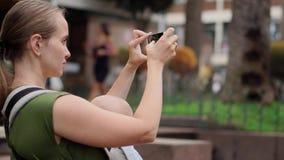 Mutter mit Baby in einem Riemen, der einen Smartphone in ihren Händen hält und ein selfie mit dem Baby nimmt stock video footage