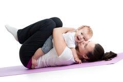 Mutter mit Baby tun die gymnastische und Eignungsübungen Lizenzfreies Stockfoto