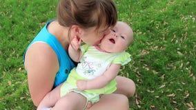 Mutter mit Babytochter auf grünem Gras stock video footage