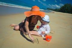 Mutter mit Babyzeichnung auf sandigem Strand Lizenzfreies Stockfoto