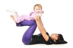Mutter mit dem Baby, das Übungen über Weiß tut Stockfotografie