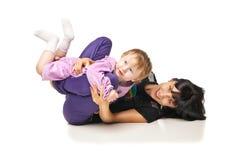 Mutter mit dem Baby, das Übungen über Weiß tut Lizenzfreies Stockfoto
