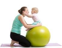 Mutter mit dem Baby, das den Spaß gymnastisch hat Lizenzfreie Stockfotografie