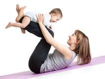 Mutter mit dem Baby, das Gymnastik und Eignung tut Stockfotografie