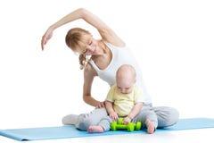 Mutter mit dem Baby, das Gymnastik und Eignung tut Lizenzfreies Stockfoto