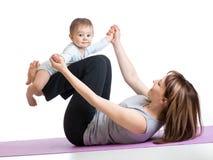 Mutter mit dem Baby, das Gymnastik und Eignung tut, trainiert Lizenzfreies Stockbild