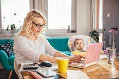 Mutter mit dem Baby, das zu Hause Büro des Laptops verwendet Stockfotos