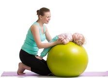 Mutter mit dem Babyhandeln gymnastisch auf Ball Lizenzfreies Stockfoto