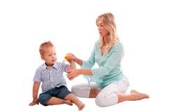 Mutter mit dem frohen Sohn, der mit Seife bubbl spielt Stockbild