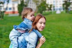 Mutter mit dem Kind auf seinem unterstützen draußen Lizenzfreies Stockbild
