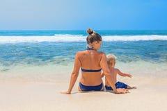 Mutter mit dem Kind, das auf dem weißen Sandstrand sitzt Stockfoto