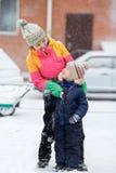 Mutter mit dem Kind, das draußen an der Straße im Winter während der Schneefälle spielt Stockfotografie