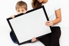 Mutter mit dem Kind, das einen Rahmen hält Lizenzfreies Stockbild