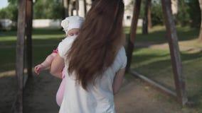 Mutter mit dem Kind, das geht, auf ein hölzernes Schwingen bei Sonnenuntergang zu fahren stock video footage