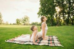 Mutter mit dem Kind, das Yogaübung tut Stockfoto