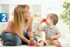 Mutter mit dem Kindersohnspiel, das Spaßzeitvertreib hat Lizenzfreie Stockbilder