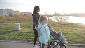 Mutter mit dem Kinderwagen und zwei Kindern, die einen Spaziergang hinunter die Stra?e machen stock footage