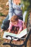 Mutter mit dem kleinen Baby, das ein Buch mit Bildern aufpasst Stockfoto