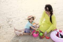 Mutter mit dem kleinen Mädchen, das auf dem Strand spielt Stockfotografie